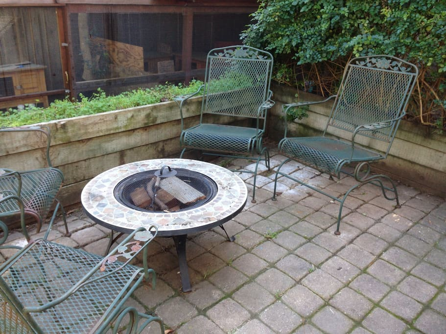 Patio seating and fire pit.  A large wooden rabbit enclosure is  in the background.