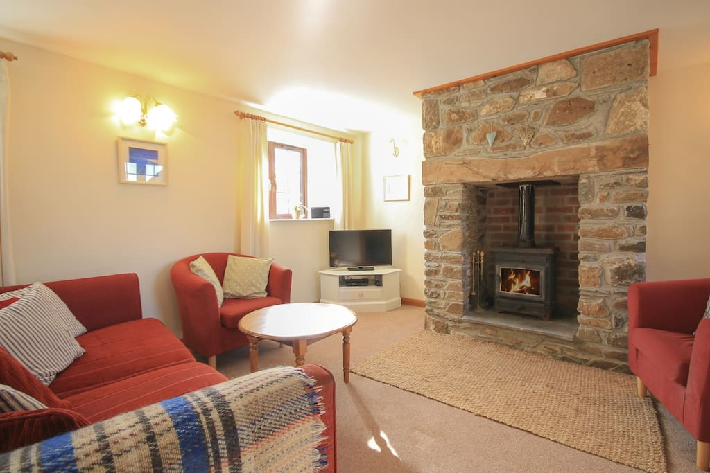 Open plan but cosy lounge and dinning room with traditional fireplace and woodburner.