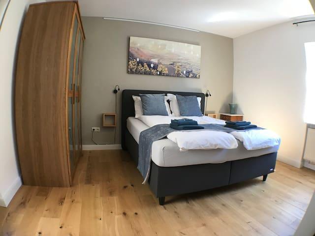 Das Schlafzimmer mit Eichenparkett und einem träumerischen Moselpanorama, gemalt von Bram de Mos.