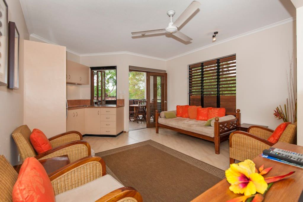Open plan living area with Kitchen, lounge chairs and day bed.