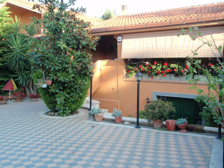 FRONT GARDEN/ ENTRANCE WITH A VIEW OF THE LARGE PATIO (COVERED BY A CURTAIN)
