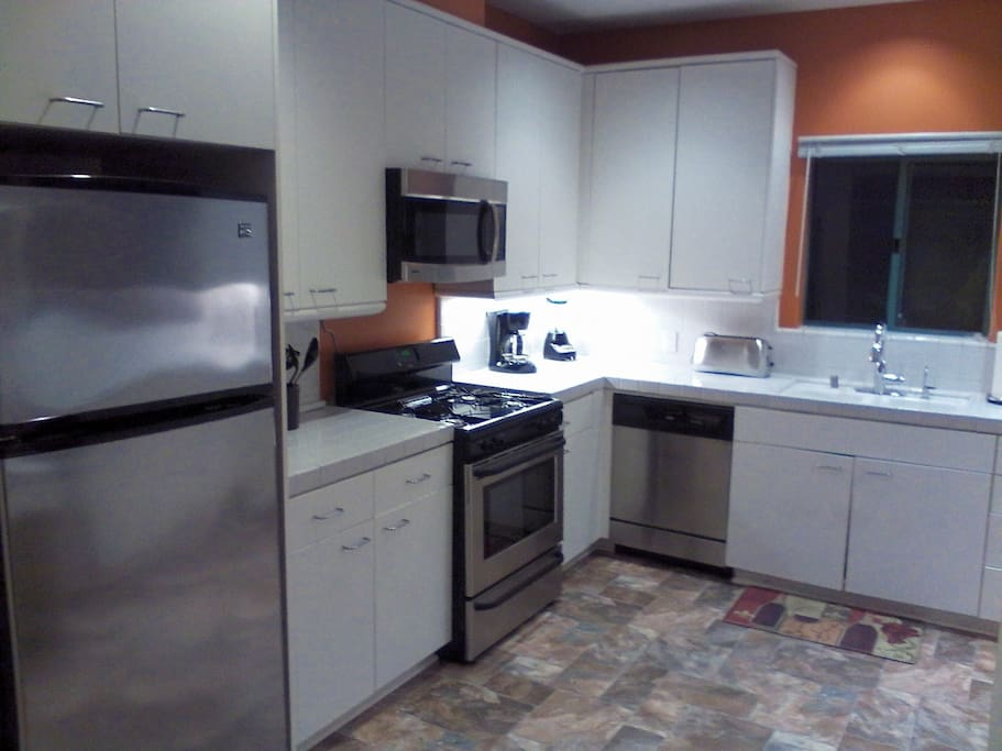 large kitchen with all stainless steel appliances.