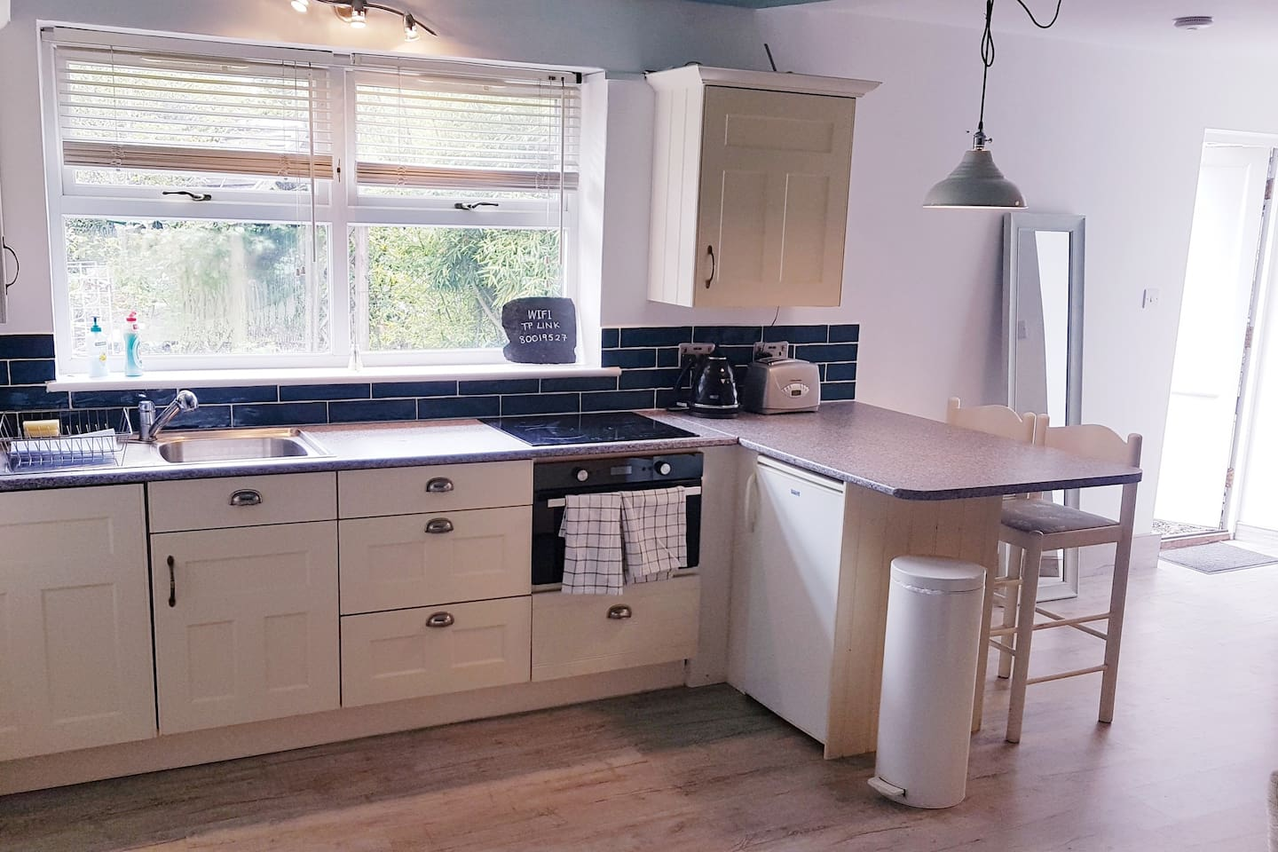 A well equipped kitchen with combination oven, induction hob, fridge and freezer.  Pretty view over the garden.