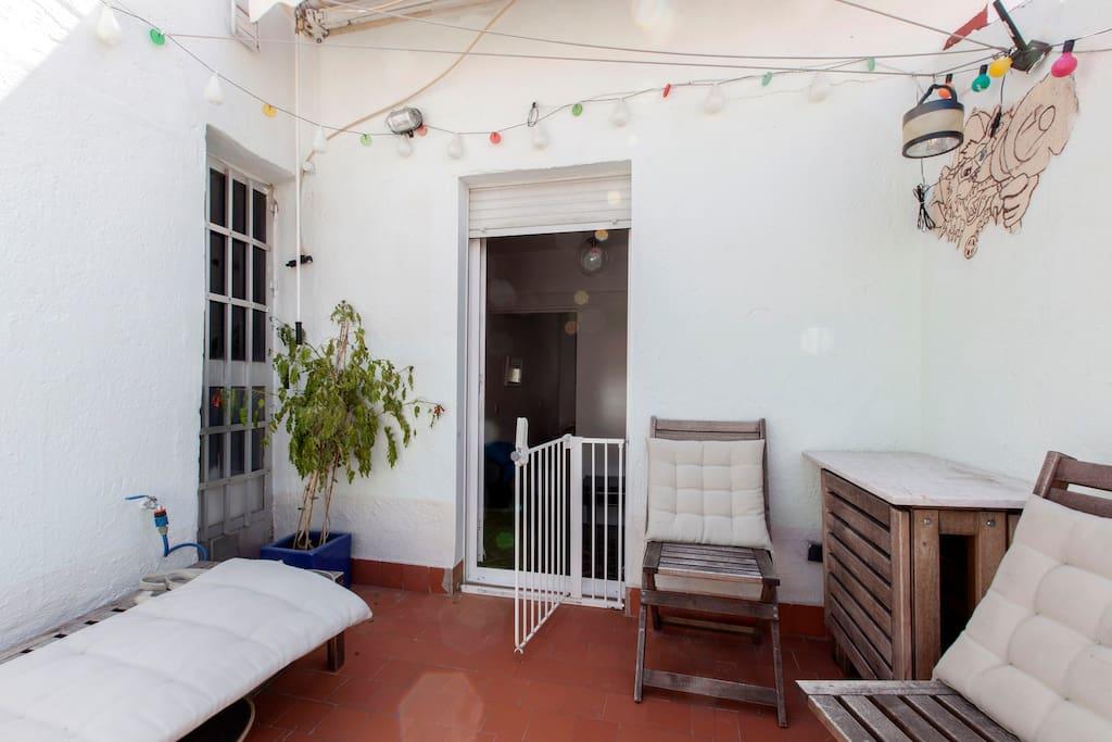 La terraza con mesa plegable, sillas, banco y tumbona.