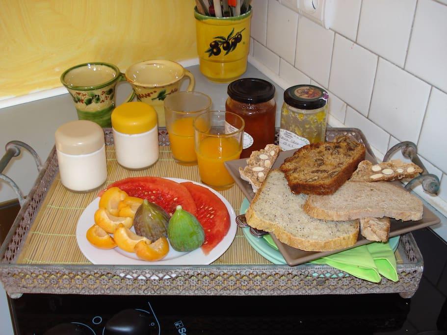 un aperçu du plateau petit déjeuner qui vous est proposé (fruits de saison, yaghourt maison, pains variés, jus d'orange frais, confitures maison