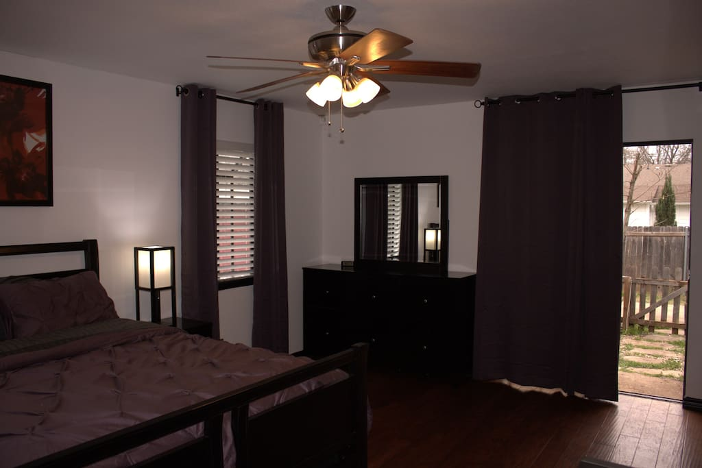 Your room, with a comfy bed, a work desk, movies and internet, and a door to the backyard.