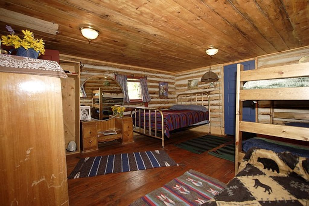 Inside the cabin with a queen bed,twin bed and bunkbed.