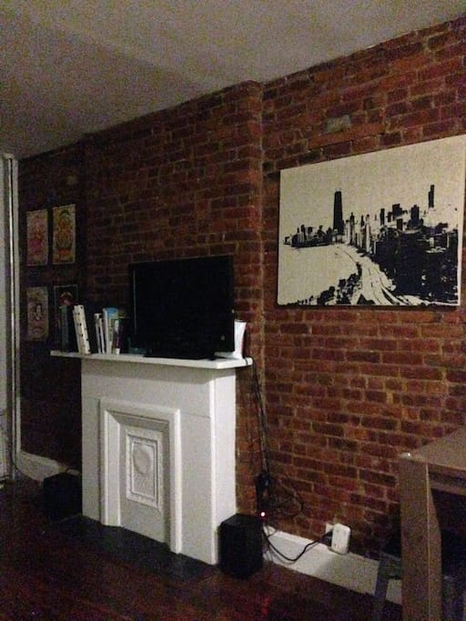 Exposed brick and TV with PS3 connected for Bluray, DVD, Netflix or Hulu