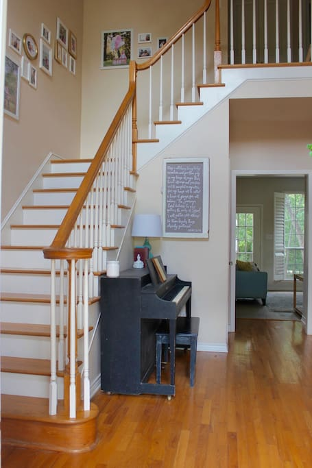 A view from the entryway. The stairs lead the 3 bedrooms upstairs. There is a half bath near the living room.