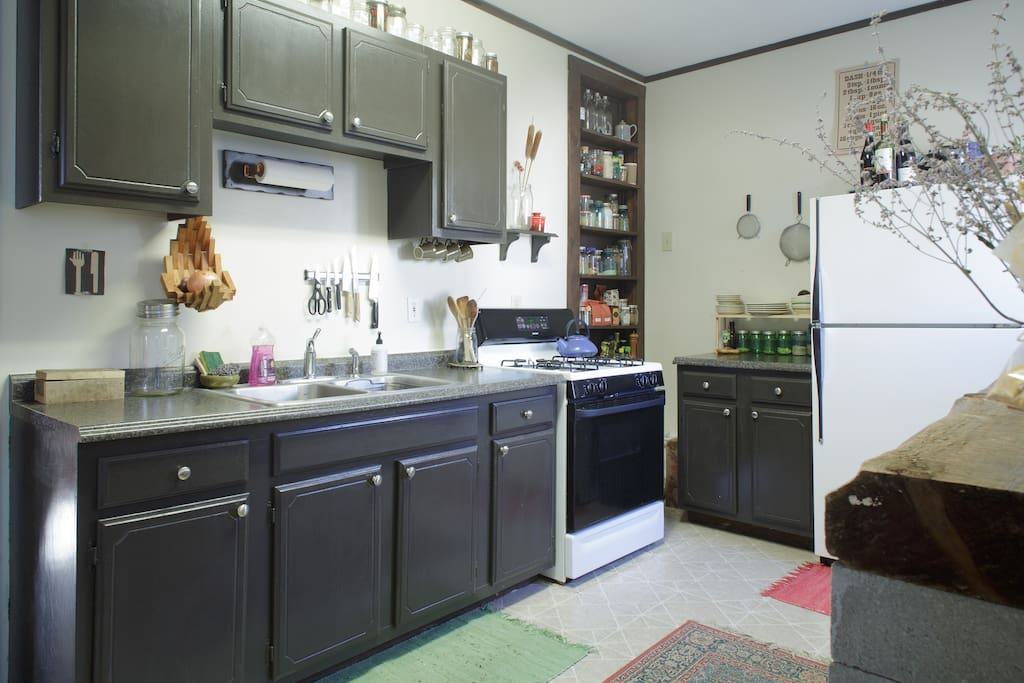 Good sized kitchen with small breakfast bar, gas range + oven, toaster, fridge, fully-stocked utensils for cooking, and french press