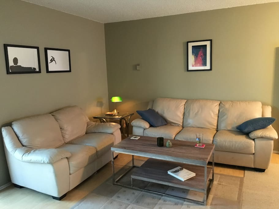 Main living room with 2 leather couches, new coffee table and hardwood floors.