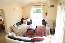 Sitting room with double aspect patio doors onto pool & garden terraces