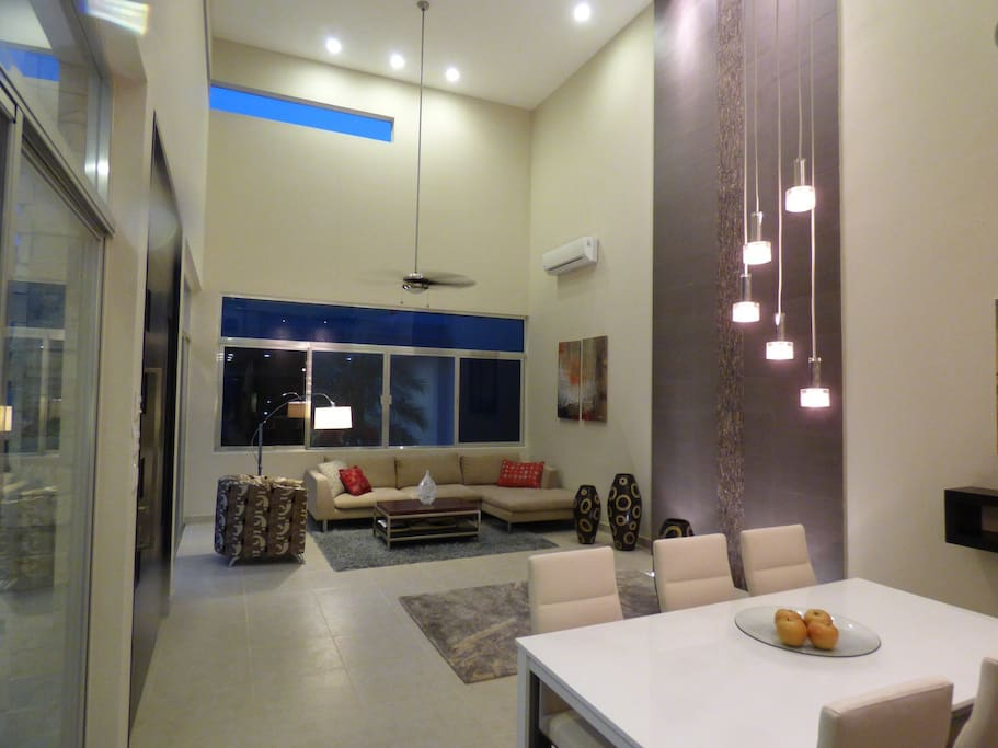 Living and dining areas with towering 20' ceiling