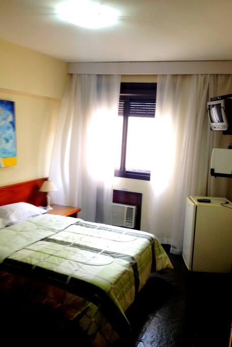 Quadro arejado com ar-condicionado, microondas e frigobar. Armário embutido e banheiro.