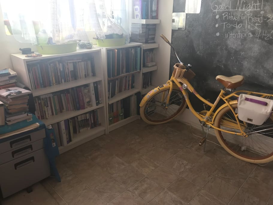 Library and beach cruiser in front of the chalkboard next to the kitchen.