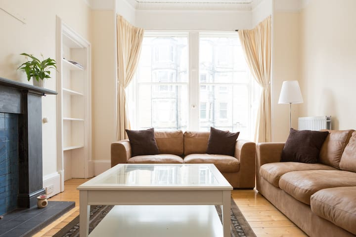 Spacious living room provides an abundance of natural light against the backdrop of Victorian architecture