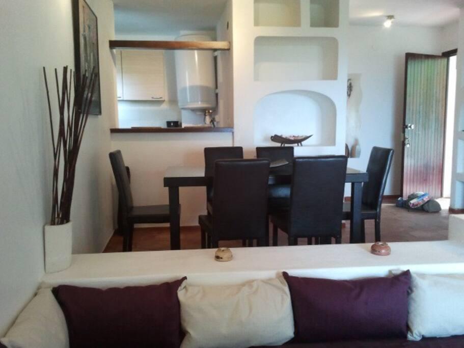 salle à manger et séjour coin télé cheminée et canapé lit