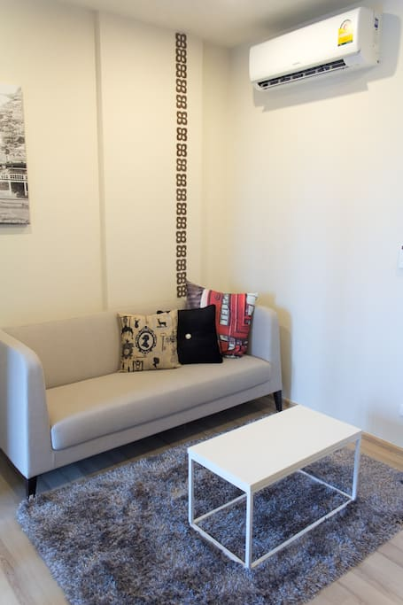 Living room furnished with couch and coffee table with air condition for your comfy.