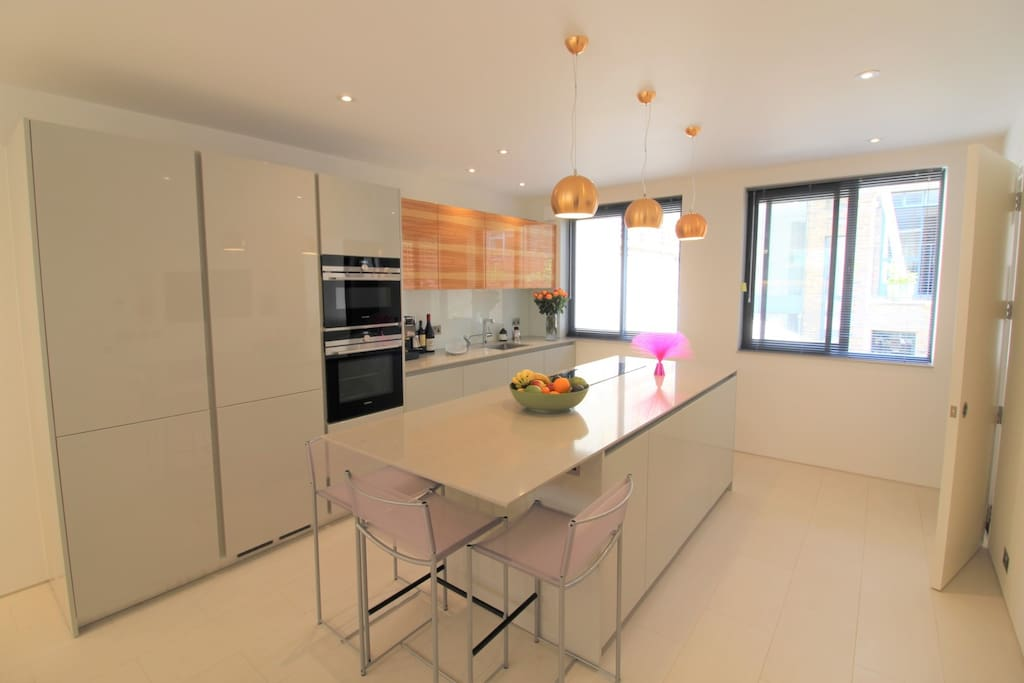 An Italian well equipped kitchen/dining room has an island breakfast bar with 3 stools as well as a dining table for 6 with 6 chairs. The kitchen is equipped with a coffee machine, dishwasher, oven, microwave oven, an induction hob, instant boiling water, toaster, fridge,  freezer with ice maker and a wall mounted TV.