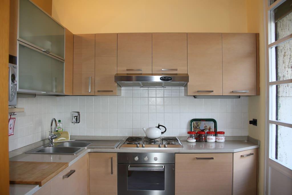Cucina con microonde, lavastoviglie e lavatrice