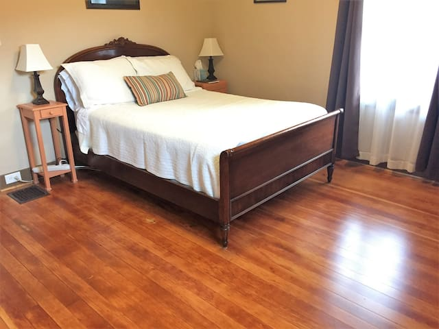 Your 12 x 12 spacious room has a double bed, ceiling fan, sitting chairs, and restored original fir hardwood floors!