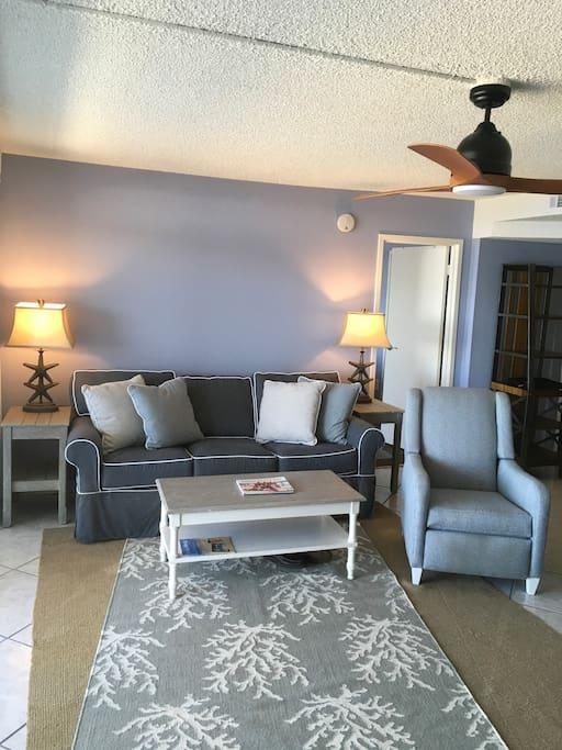 Living room has tasteful furniture with beach feel, queen-sized sleeper sofa