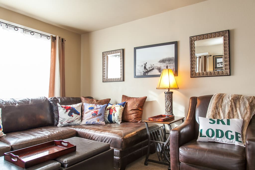 Living room, with 55 inch TV and leather comfy sleeper sofa.