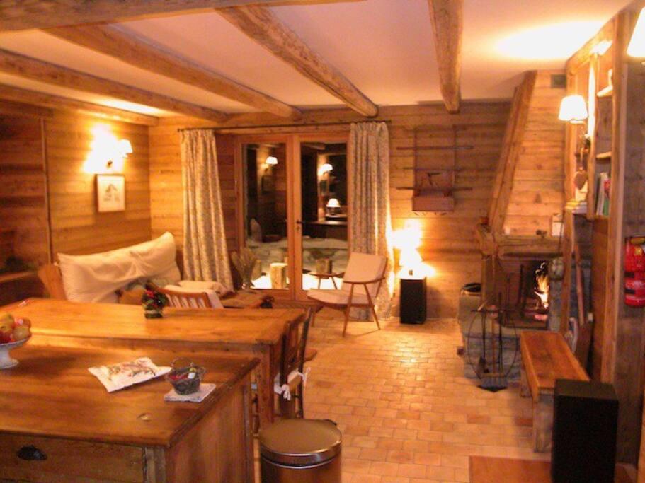 Salle de séjour rez de jardin la nuit cheminée