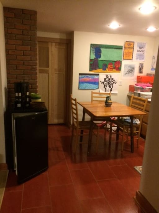 There is a common eating area with a refrigerator, sink, coffee maker and a toaster oven...