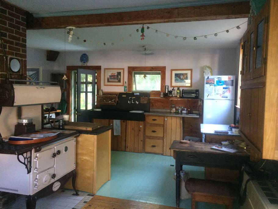 "Sunny farm kitchen, slate sink, wood cook stove, live edge shelving... ""normal"" gas stove not visible around the wood one."