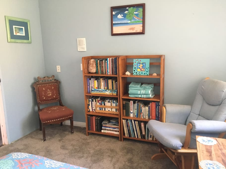 Beach themed decor, plenty of books to read and a comfy rocker to relax in.