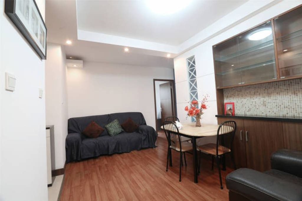 Spacious living room with a big sofa and dinning table etc
