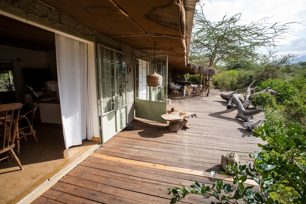 Spacious balcony, surrounded by dense African vegetation (acacia trees, bushes,...)