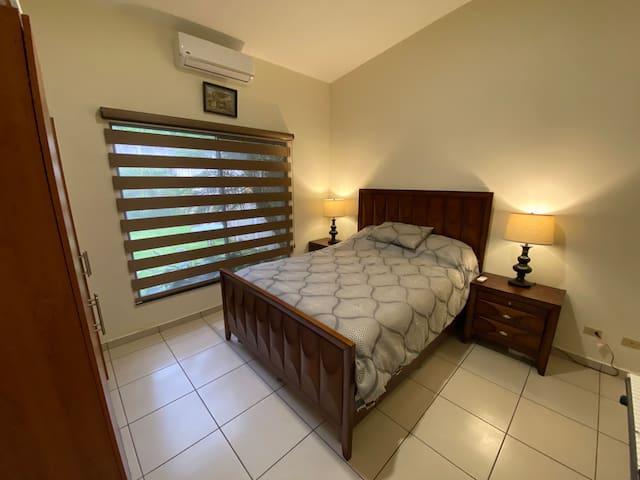 Cuarto con cama queen, clóset, aire acondicionado y baño privado