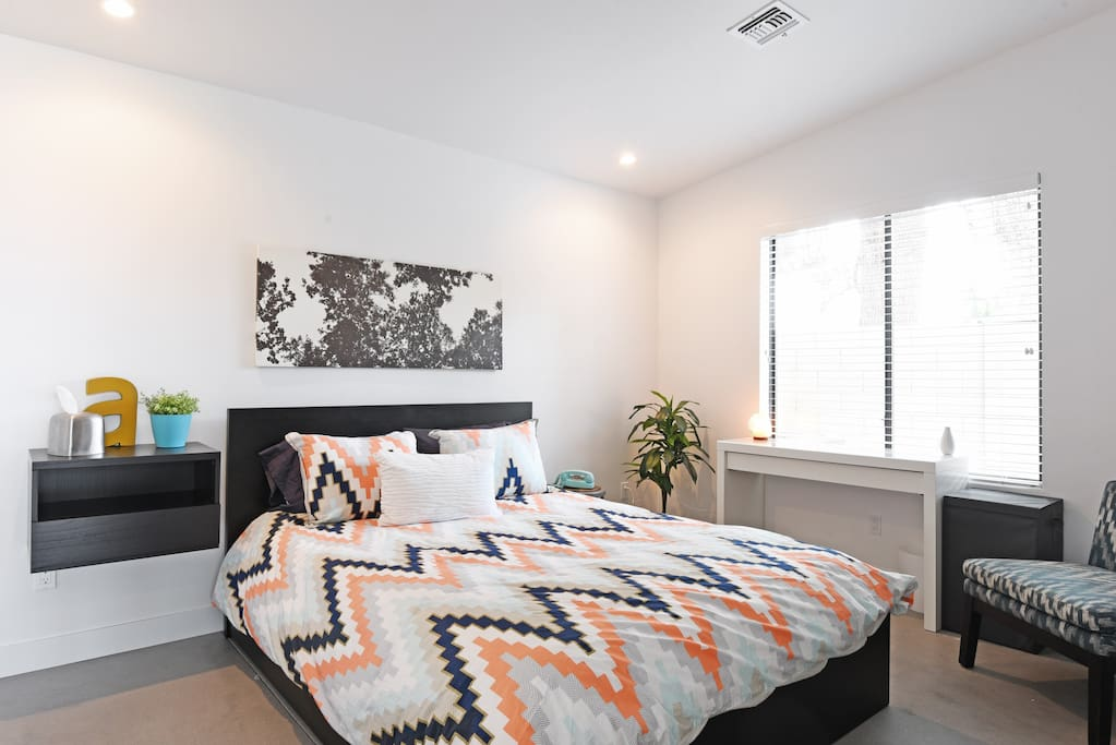 The comfortable bedroom has ample space to unpack and feel at home. The desk can be used as a vanity or a workspace.