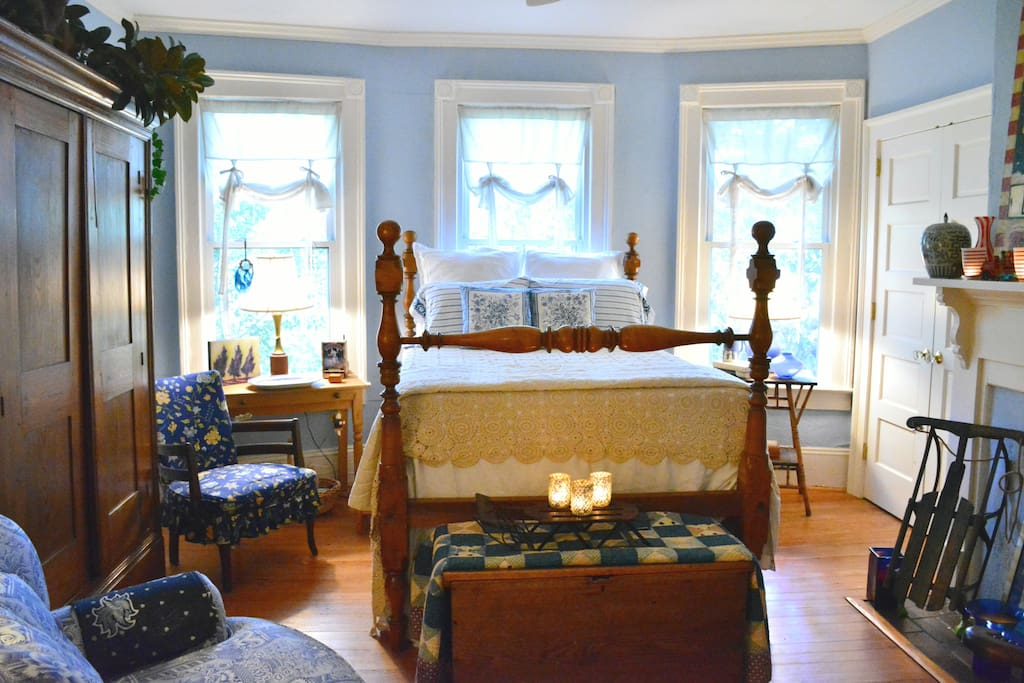 """""""Blue bedroom"""" - Antique Four Poster bed from the Durkee Estate.  19th century NC wardrobe.  French antique linens. NC hand crocheted coverlet. Hand carved mahogany chair. Hand painted Garouche by NYC designer, Marshall Watson."""