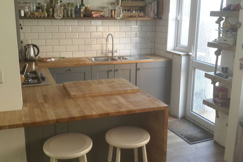 Newly furbished kitchen with oak worktop surface and breakfast bar.
