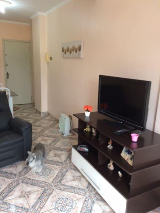 """Sala com dois ambientes: de estar com sofá/cama para 2 pessoas + TV 42"""" e vista para o mar; sala de jantar acoplada à cozinha americana"""