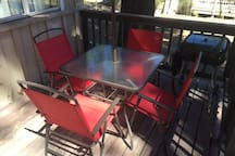 Patio table with 4 patio chairs, umbrella and a BBQ grill.