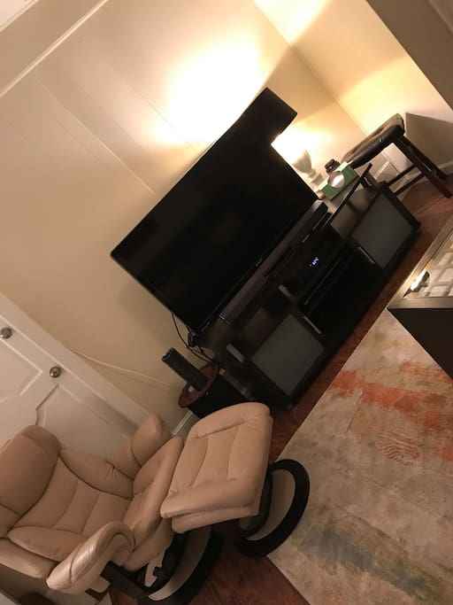 T.V., stand, leather recliner and ottoman
