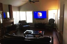 Living room with 65 inch SONY TV and surround sound. Fireplace and comfortable couch.