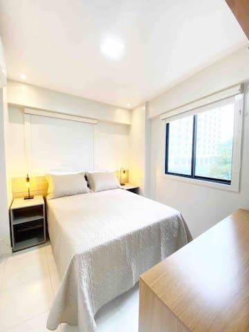 Suíte com cama de casal, iluminação aconchegante e cortinas BlackOut.