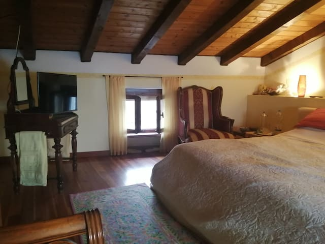 Large room with double and single bed. Ampia camera con letto matrimoniale e uno singolo.