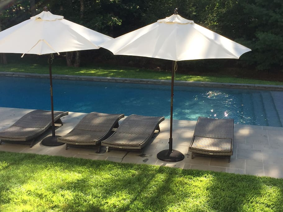 The expansive pool is luxurious with chairs with lounge chairs and umbrellas for a good time poolside.