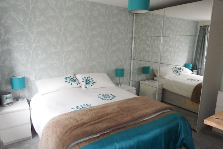 Cosy bedroom with king size bed and large mirror doored wardrobe