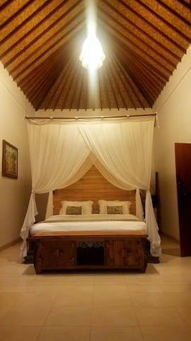 Bedroom #3 upstairs with king-sized bed, private bathroom, A/C, and private balcony overlooking the pool and jungle.