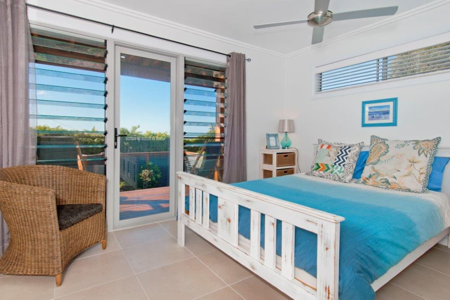 comfortable queen size bed with ceiling  fan & plantation shutters
