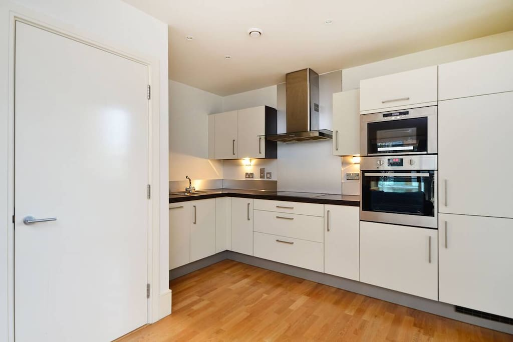 The kitchen area with dishwasher, electric hobs and built in microwave/oven