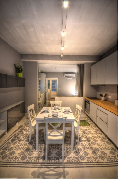The property is well-spaced out, with the kitchen and bedroom separated by a low partition wall/counter and curtains.