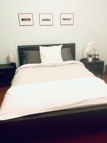 The front bedroom has a queen sized bed with soft bedding & side tables, each with lamps, for comfortable sleep and relaxation. Photographs by a local Alachua county artist of nature sites are hung above the bed. Black out curtains cover the windows.